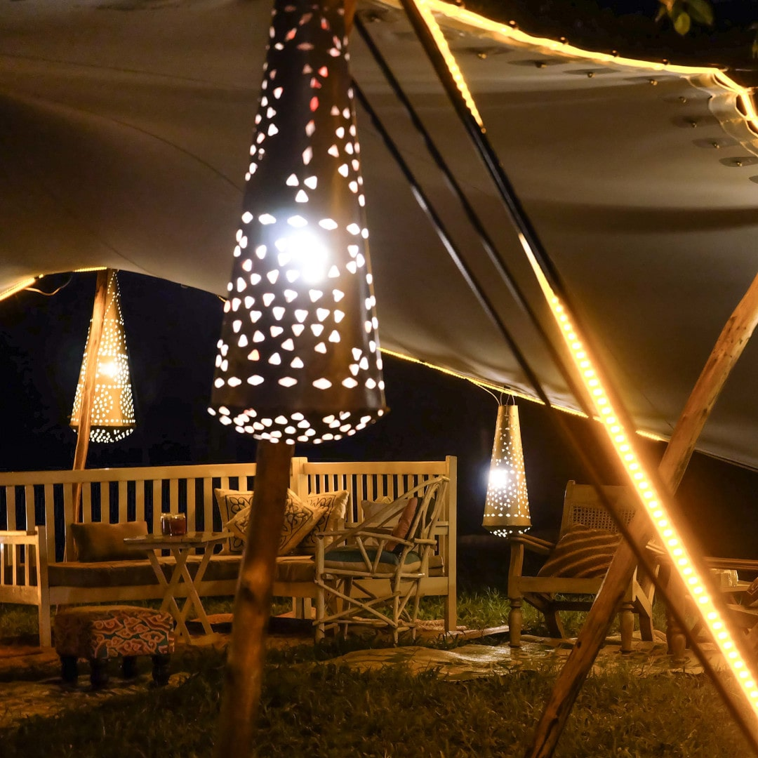 namiot stretch oświetlony lampionami nad kompletem wypoczynkowym